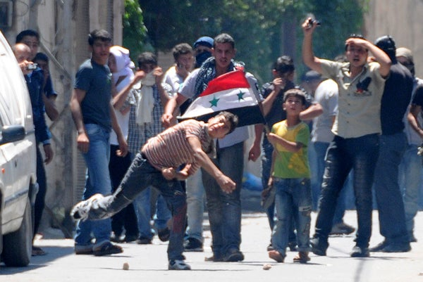 Anti-regime youths in Syria throw stones at security forces