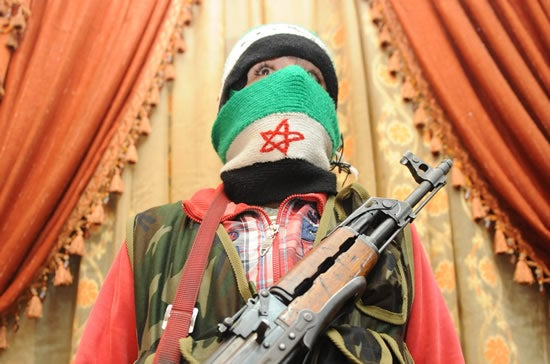 An armed Free Syrian Army rebel stands inside a house in the north Syrian city of Binnish on February 15, 2012.