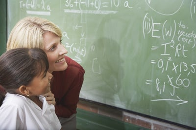 Teacher and student in classroom at chalkboard