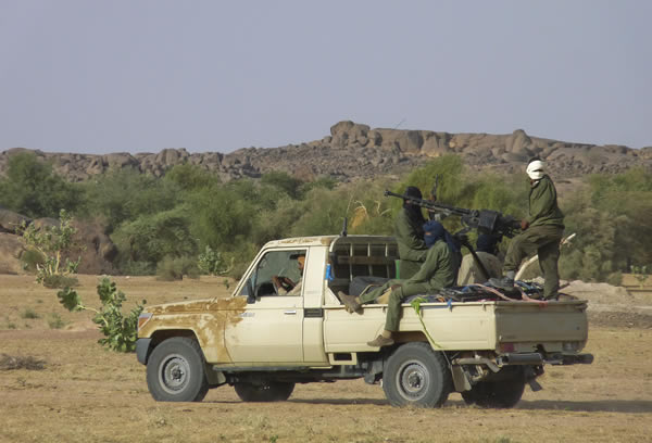 A file photograph dated October 18, 2011, shows Tuareg rebel fighters moving through northern Mali on a pick-up truck with a mounted heavy machine gun, near Kidal, Mali.