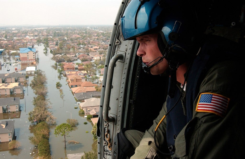Coast Guard Petty Officer Shawn Beaty looks for survivors in the wake of Hurricane Katrina. Beaty is a member of a helicopter rescue crew sent from Florida to assist in search and rescue efforts. (Photo: PA2 NyxoLyno Cangemi/UPI Photo/Newscom)