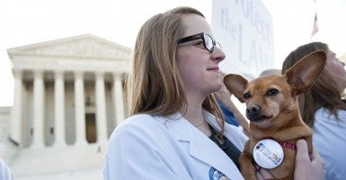 Georgetown medical student Kate Prather holds her dog Elie during a rally outside the U.S. Supreme Court as the court begins hearing arguments on the constitutionality of President Obama's health care bill in Washington, D.C. on March 26, 2012.  (Photo: UPI/Kevin Dietsch)
