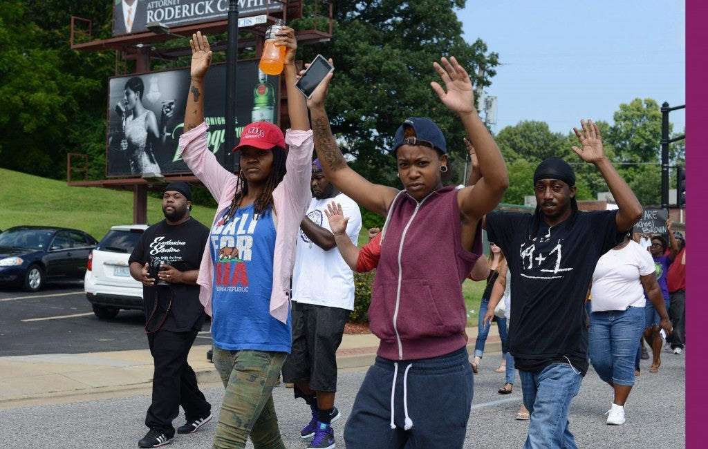 Mya White, in hat, shown in this August 11, 2014 file photo, was shot in the head during a demonstration in Ferguson, Missouri on August 13, 2014. White was shot in the head by a passing car as people demonstrated. (Photo: UPI/David Broome)