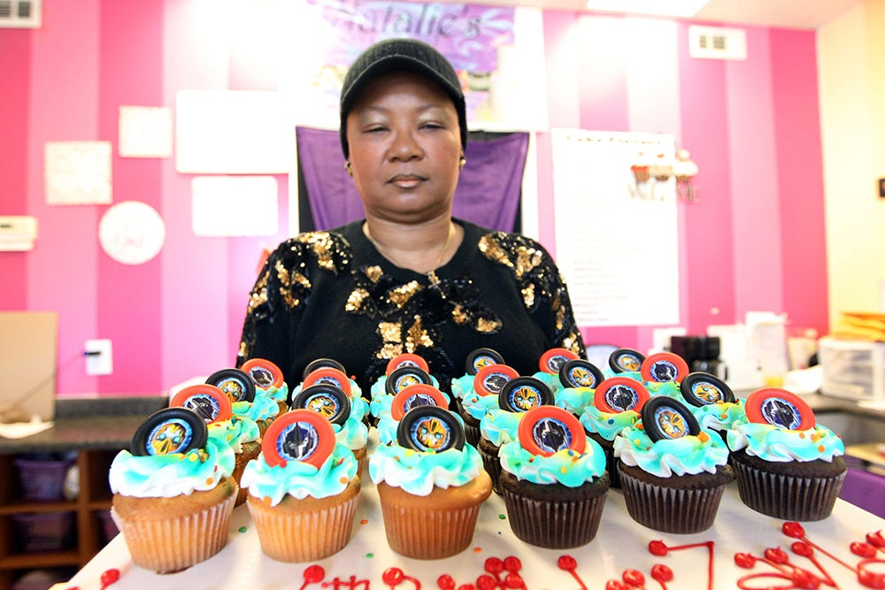 Valencia Clay, a worker at Natalie's bakery, shows off freshly made cupcakes. Over 20 businesses were set ablaze and many more had store front windows broken on Nov. 24. (Photo: Bill Greenblatt/Newscom)