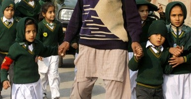 Children are escorted from a school in Peshawar, Pakistan after an attack by Taliban gunmen on on Dec. 16, 2014. Taliban insurgents killed more than 120, mostly students, in a morning terrorist attack on the military-run school in northwest Pakistan. (Photo: UPI/Sajjad Ali Queshi)