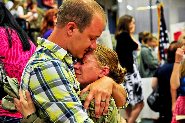 Spc. Jessie Nelson, 4th Brigade, 2nd Infantry Division, hugs her husband, Matt, after her eight-month deployment to Afghanistan in support of Operation Enduring Freedom in 2013. (Photo: U.S. Army photo by Sgt. Kimberly Hackbarth, 4th SBCT, 2nd ID Public Affairs Office)