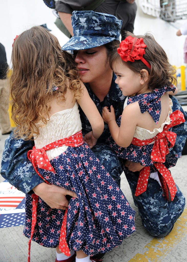 U.S. Navy Hospital Corpsman Jerrilynn Sweat hugs her daughters during a homecoming ceremony in San Diego, Calif., Sept. 21, 2010  following a five-month deployment to Vietnam, Cambodia, Indonesia and Timor-Leste. (Photo: DoD photo by Mass Communication Specialist 2nd Class Chelsea Radford, U.S. Navy/Released)