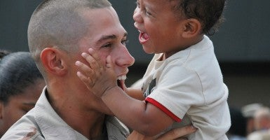 A U.S. Navy Seabee is welcomed home by his son in Gulfport, Miss., July 21, 2010, after returning home from a five-month deployment to Afghanistan in support of the surge ordered by President Barack Obama. (Photo: U.S. Navy photo by Equipment Operator 3rd Class Mikayla Mondragon/Released)