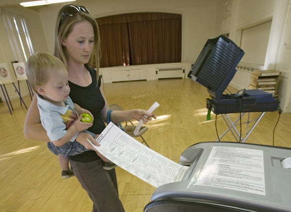 Young mother and baby inserts completed ballot for Congressional election