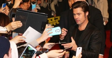 Brad Pitt signs an autograph during an event in Seoul on Nov. 13, 2014, to promote his new movie, 'Fury.' (Photo: Yonhap/Newscom)