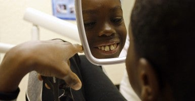 Tra'Vaughn Harrington, 10, checks out his repaired front teeth. (Photo: Newscom)
