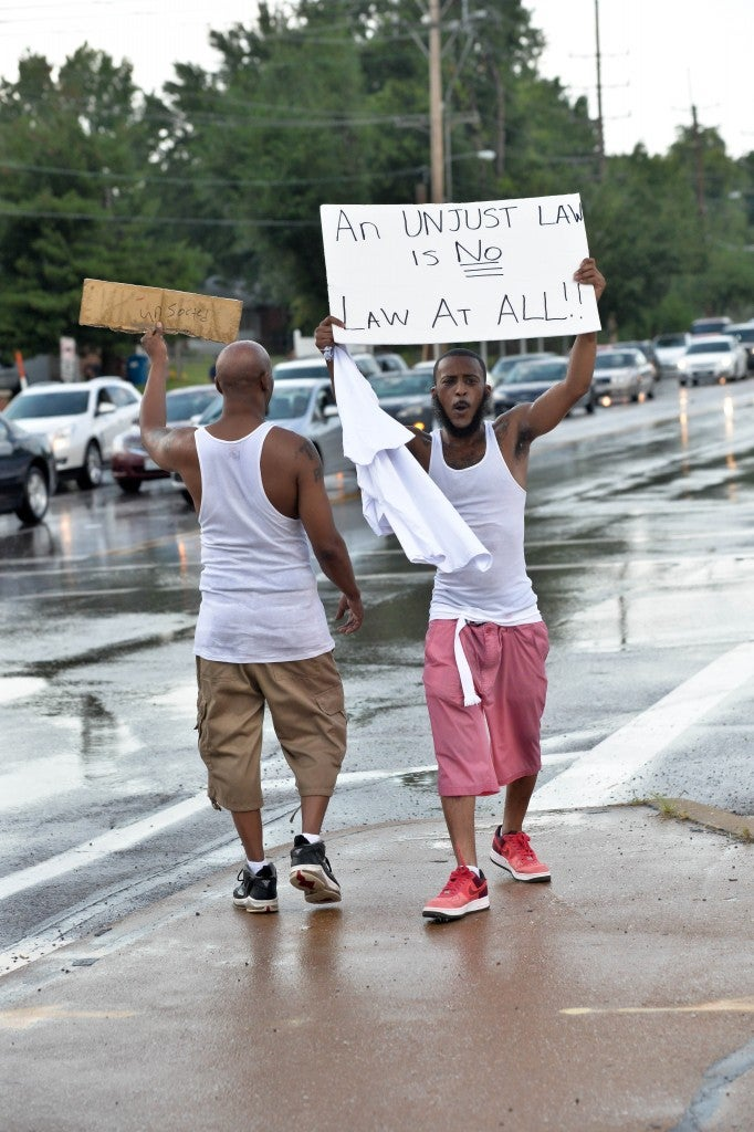 Protesters hold a peaceful demonstration of their displeasure during the second day of protests in front of the QT that was burned to ruins the night before during the riot. (Photo: Richard Ulreich/ZUMA Wire/Newscom)