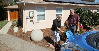 Oscar and Janet Valent connect their electric vehicle charging cable mounted on the front of their green energy home in Carlsbad, Calif. (Photo: Charlie Neuman/UT San Diego/Newscom)