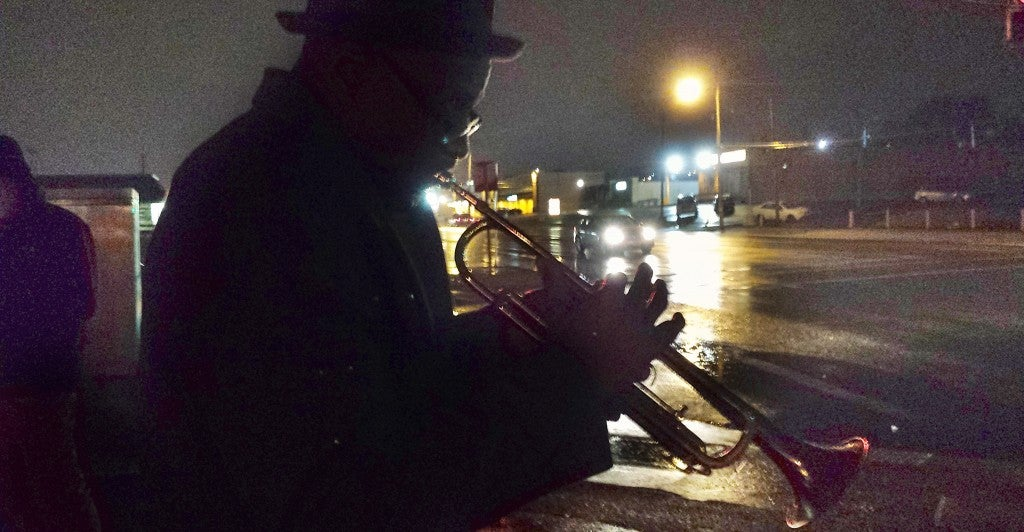 Eugene Gillis, 56, plays his melancholy jazz trumpet on West Florrisant Ave. in Ferguson, Mo. Gillis, a GM autoworker, says he's doing his part to ''bring down the temperature'' and calm frayed nerves. (Photo: Mitch Potter/Newscom)