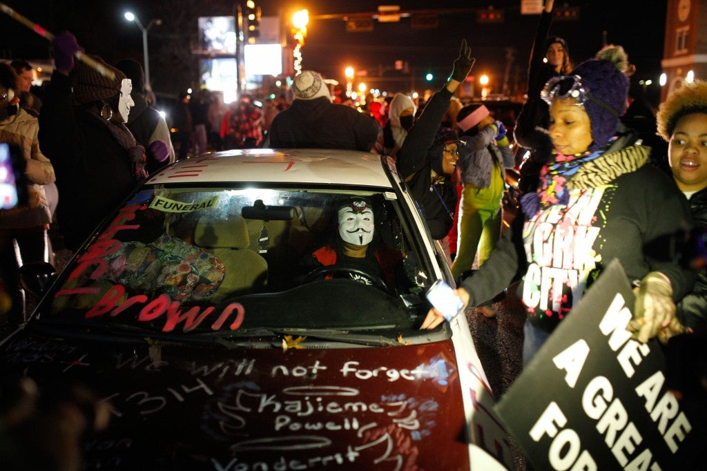 A demonstrator drives through a crowd of protesters across the street from the Ferguson police station. (Photo: Raffe Lazarian/Newscom)