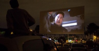 Chris McConnell, 18, of West Palm Beach, watches the movie ''The Interview'' at the Lake Worth Drive-In on Christmas Day. (Photo: Madeline Gray/Newscom)