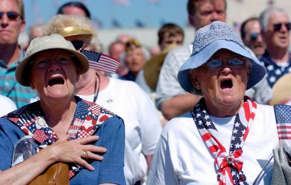 Sisters Leora Marcotte of Denver, 76, left, and Marian Butler of Omaha, 75, sing the National Anthem during the World War II Memorial dedication ceremony in Washington D.C. in 2004. Both of their husbands served in World War II. Leora's husband passed away in 2000. Ray Butler attended the dedication. (Photo: Bahram Mark Sobhani/San Antonio Express-News/Newscom)