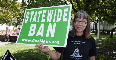 An protestor calling for a state wide ban of fracking stands outside of the New York State Fair in Syracuse, NY. (Photo: Zach D. Roberts/Newscom)