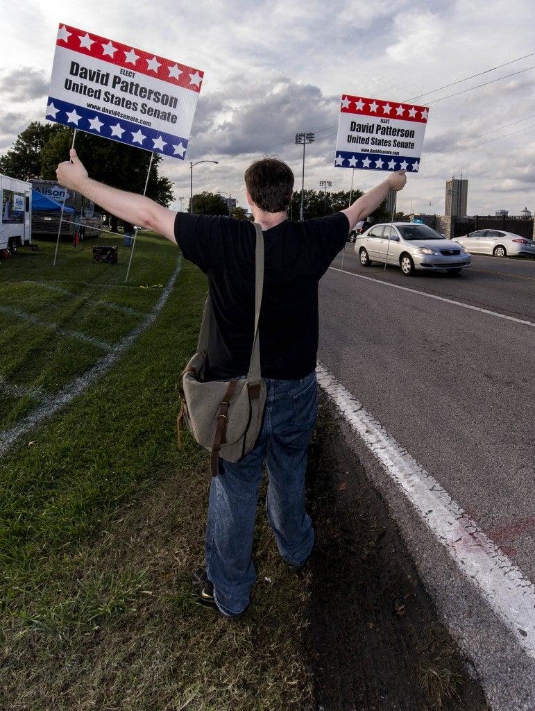 Warren Taylor holds a sign for Libertarian candidate David Patterson. (Photo: Newscom)