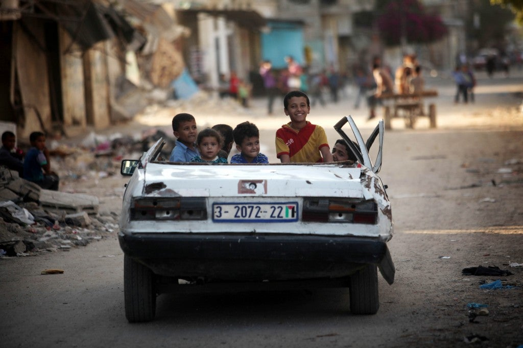 Palestinian children are driven by their father through a bomb damaged area of Beit Hanoun in their car with no roof.  (Photo: Majdi Fathi/NurPhoto/Newscom)