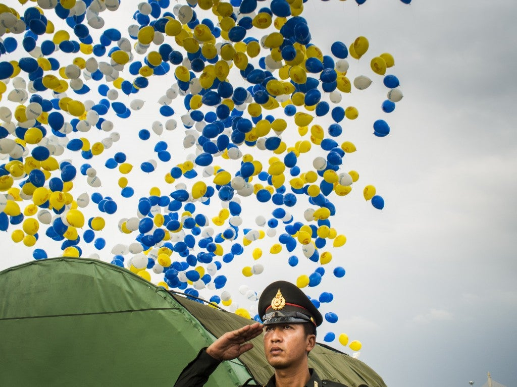 A Thai police officer salutes as balloons are released at the end of the Trooping of the Colors parade on Sanam Luang in Bangkok. (Photo: Jack Kurtz/ZUMA Press/Newscom)