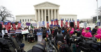 People protest outside the U.S. Supreme Court on the morning of oral arguments in King v. Burwell, a challenge to the Affordable Care Act. (Photo: Brian Cahn/ZUMA Press/Newscom)